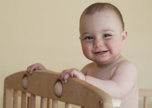 Baby standing in a cot